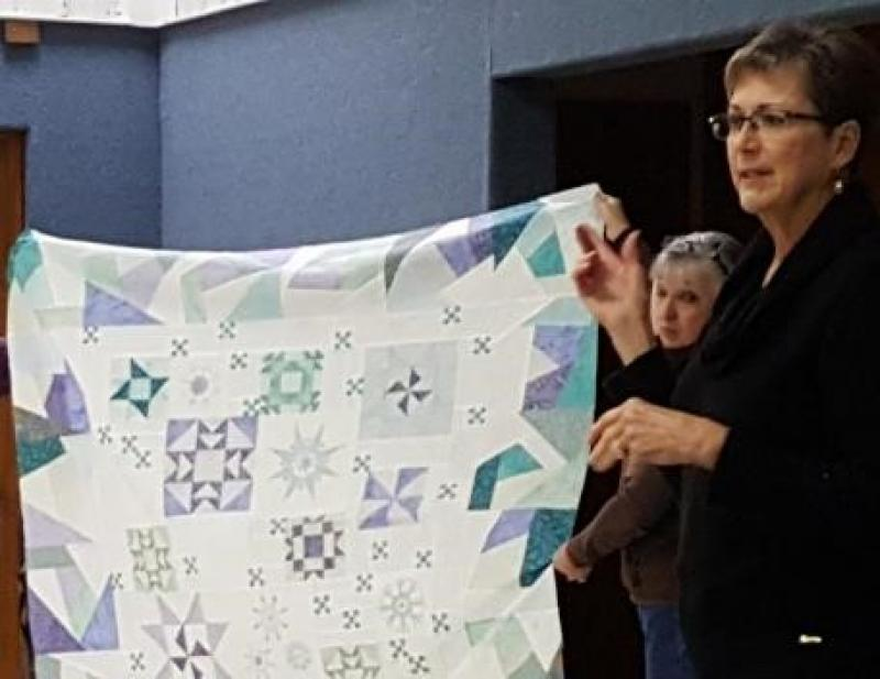 This quilt top is becoming a winter scene of blocks and embroidered snowflakes.