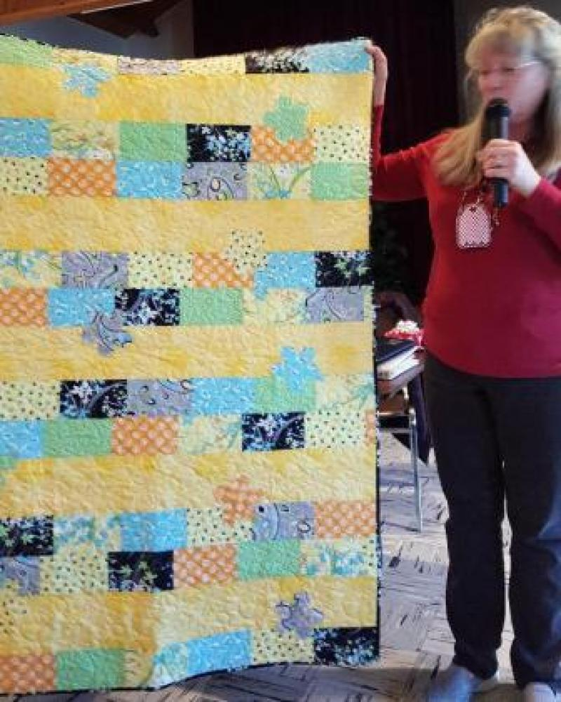 Carol L  with a children's quilt