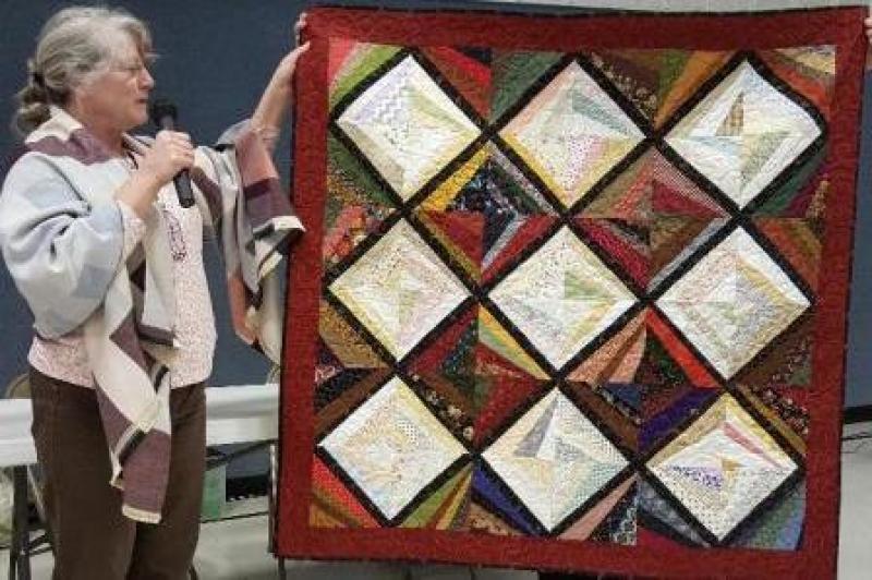 Carol shows her strip pieced scrappy quilt