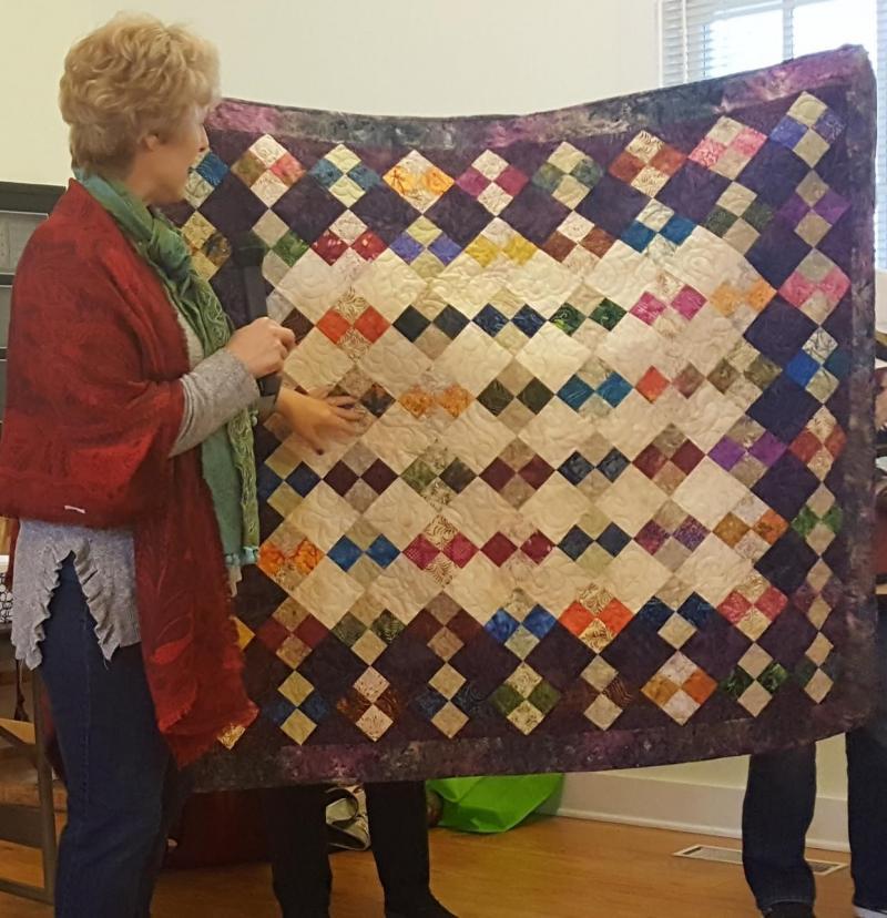 Tricia has a UFO purple batik 4-patch quilt done!